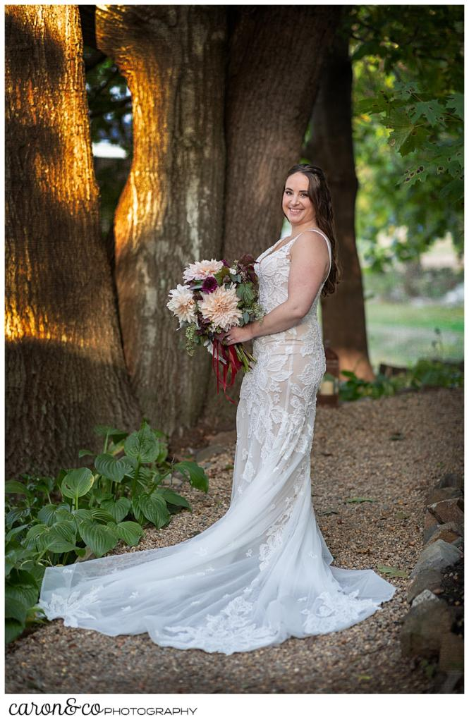 full length bridal portrait of a bride standing on a wooded path, holding a bouquet of blush and dark red dahlias