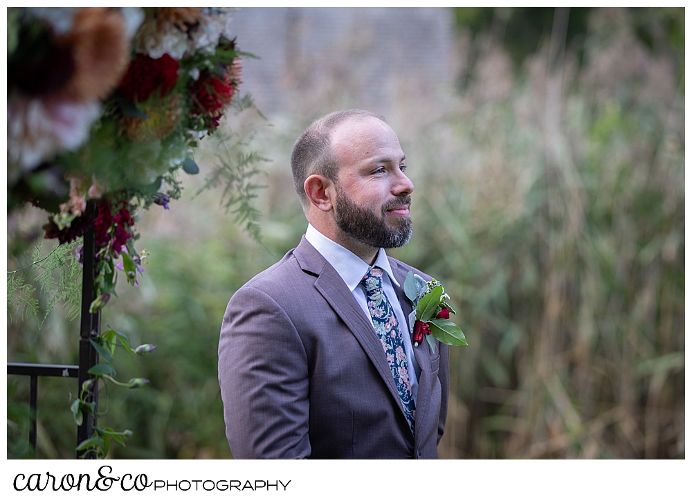 a groom wearing a brown suit, with a flowered tie, stands waiting for his bride to walk down the aisle during a charming Kennebunkport Maine wedding ceremony