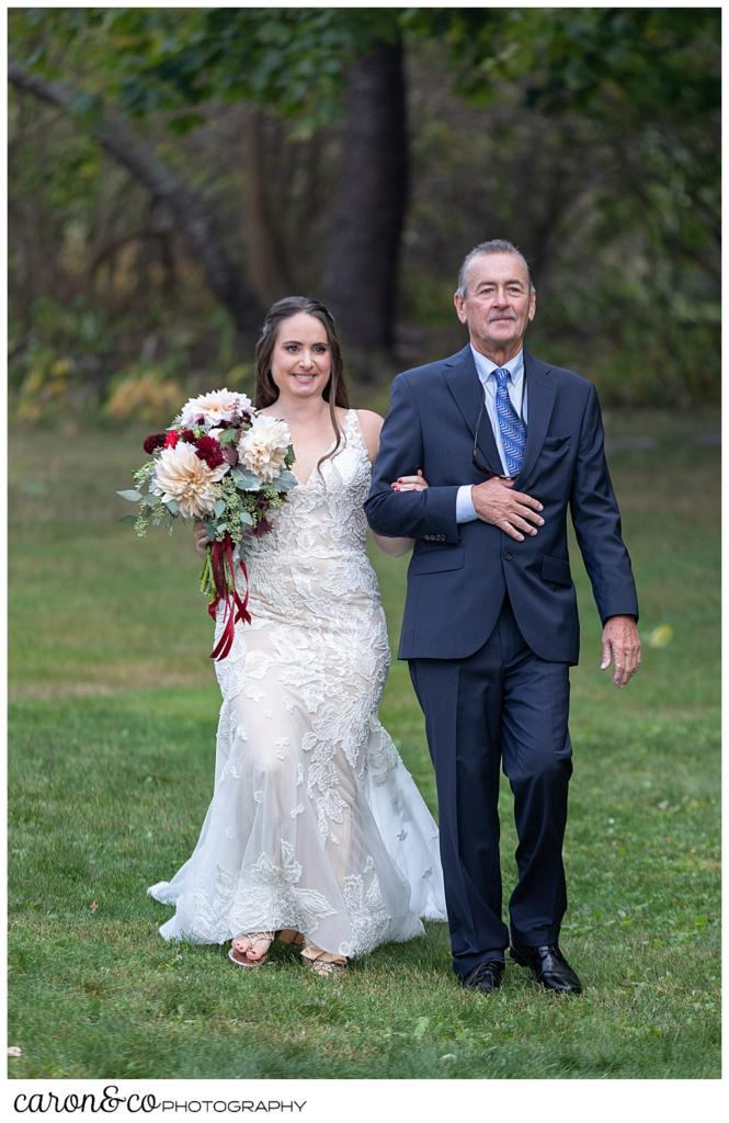 a bride and her father walk towards the ceremony site during a charming Kennebunkport Maine wedding