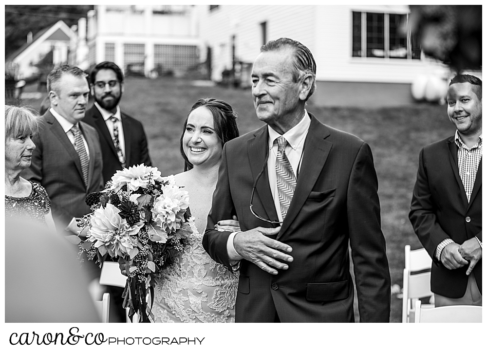 black and white photo of a bride and her father walking down the aisle during a charming Kennebunkport Maine wedding ceremony