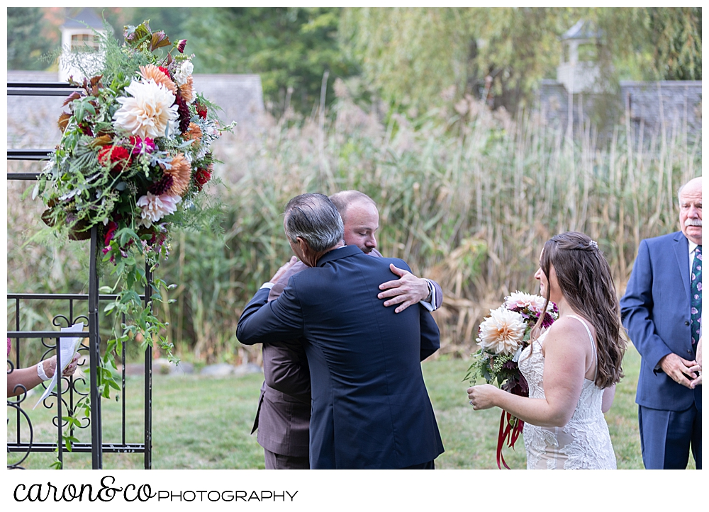 the father of the bride hugs the groom at the flowered arbor at a charming Kennebunkport Maine wedding ceremony