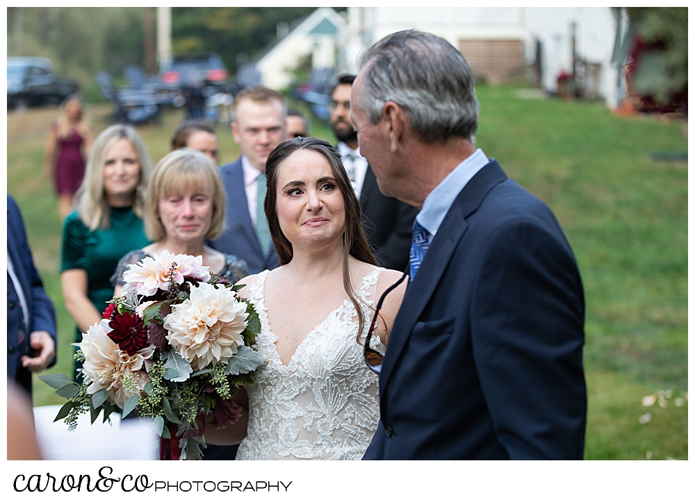 a bride looks at her father, as they reach the ceremony site for a Kennebunkport Maine wedding