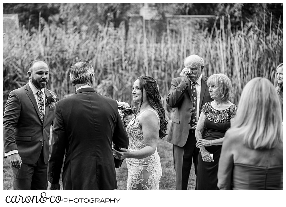 black and white photo of the father of the bride handing the bride off to the groom, at a charming Kennebunkport Maine wedding ceremony