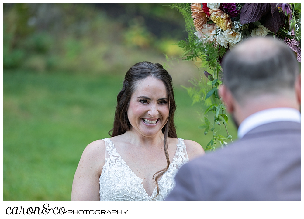 a bride smiles at her groom during their charming Kennebunkport Maine wedding ceremony