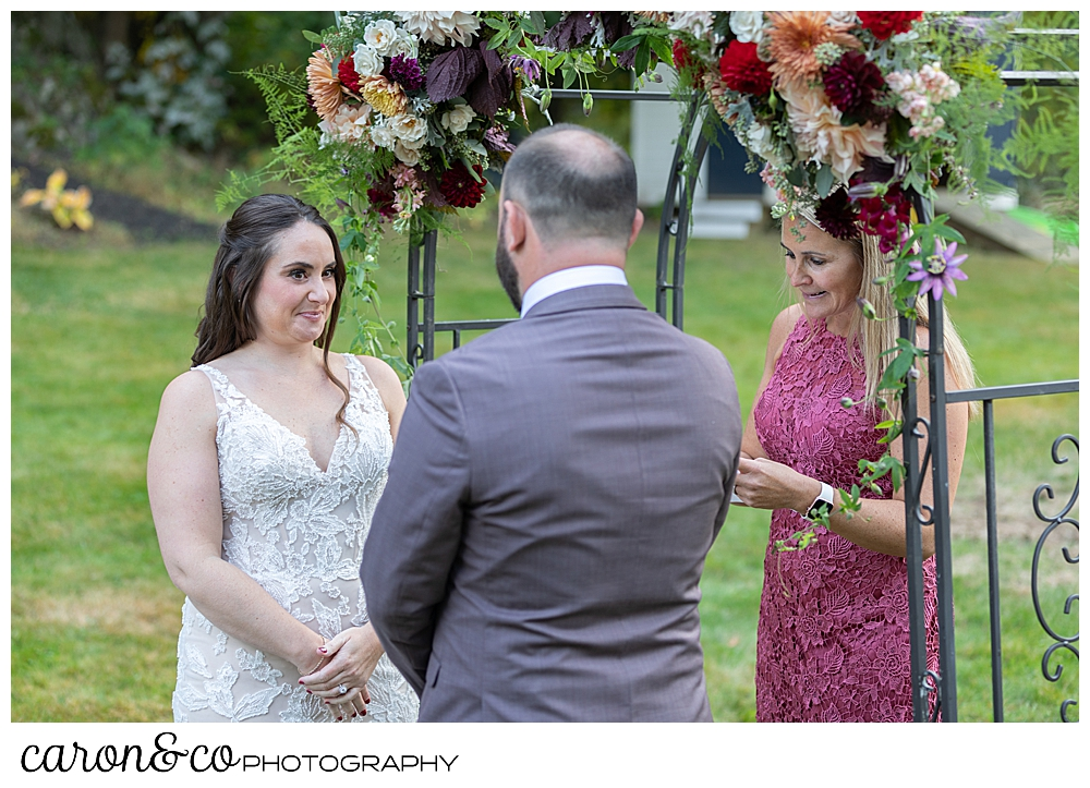 bride and groom standing in front of an arbor, during their wedding ceremony