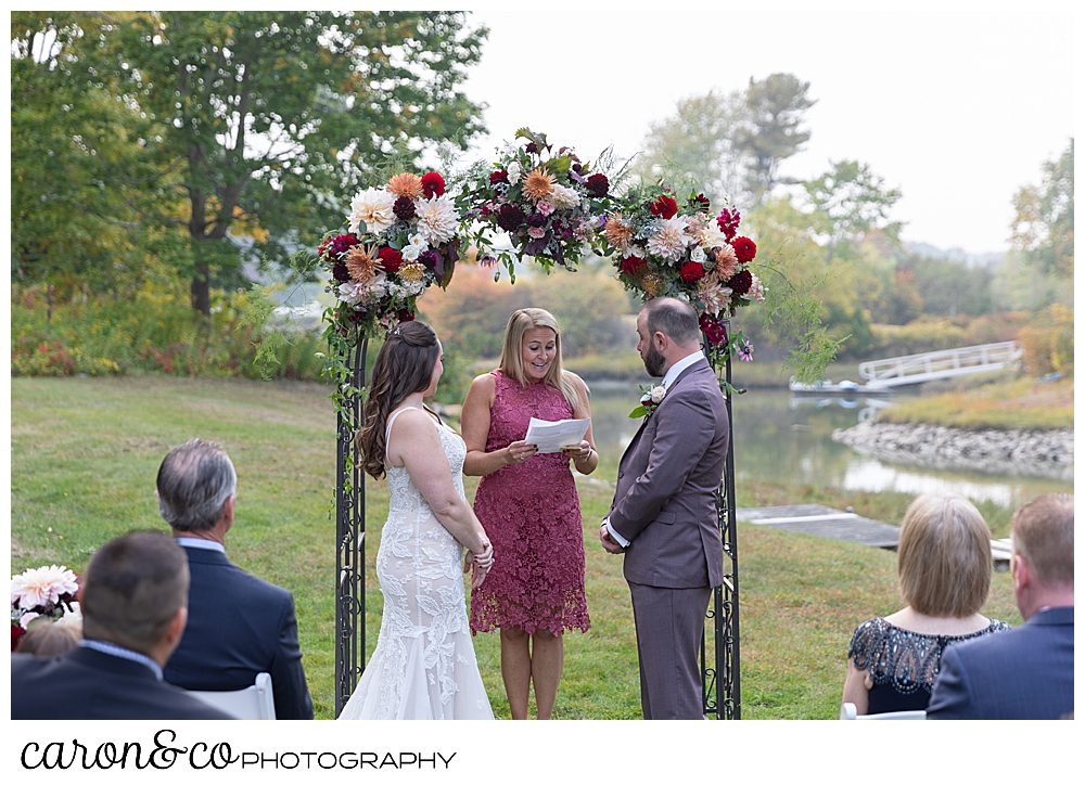a bride and groom stand before their officiant at a charming Kennebunkport Maine wedding ceremony