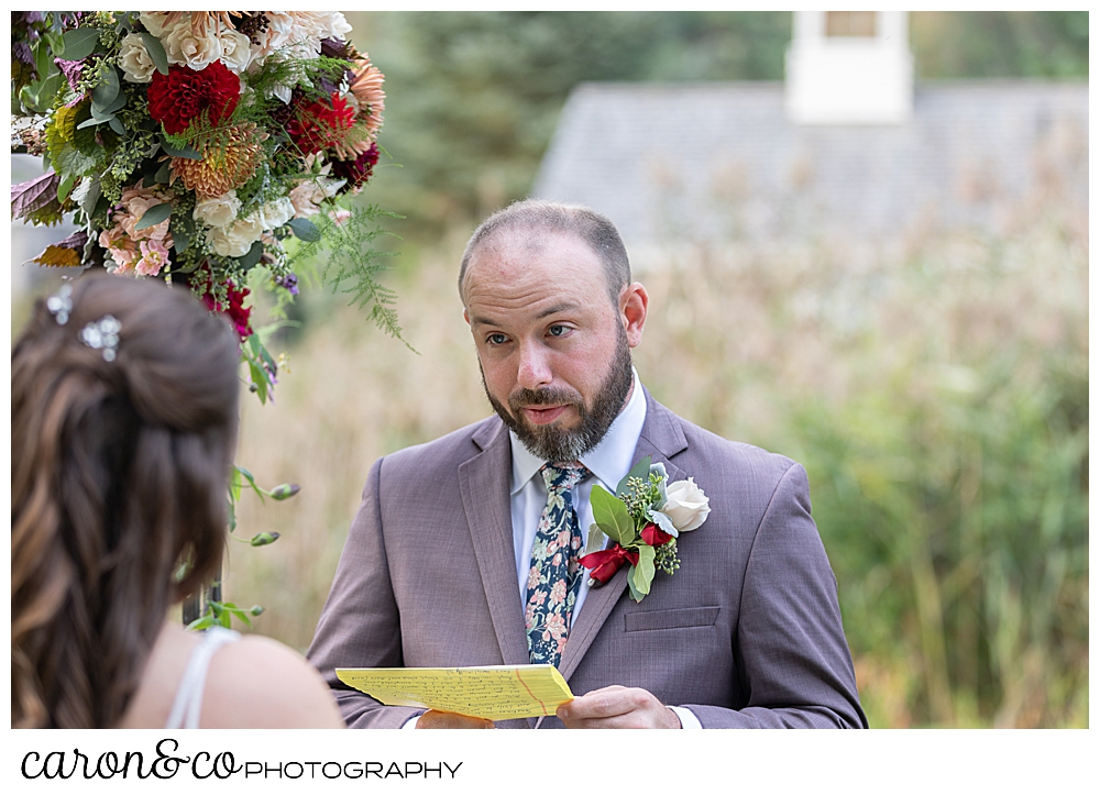 a groom reads his vows to his bride at their charming Kennebunkport Maine wedding ceremony