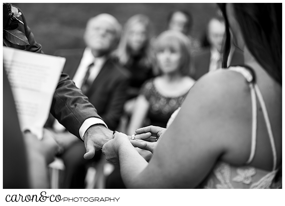 black and white photo of a bride putting the wedding band on the groom's finger