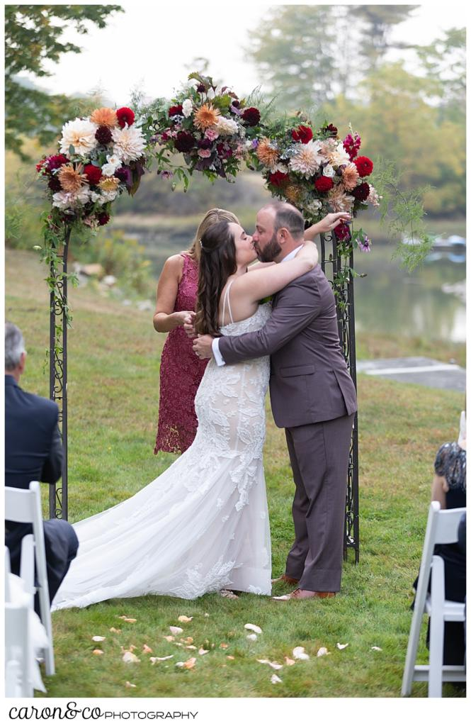 bride and groom's first kiss at their charming Kennebunkport Maine wedding ceremony