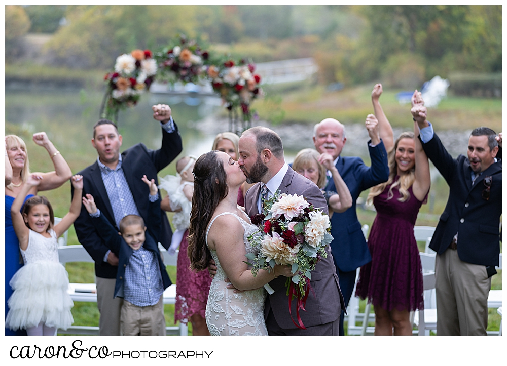 a bride and groom kiss, while their guests cheer behind them at a charming Kennebunkport Maine wedding ceremony