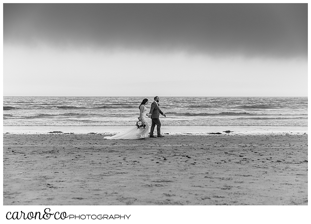 black and white photo of a bride and groom walk along the water's edge in Kennebunk Maine