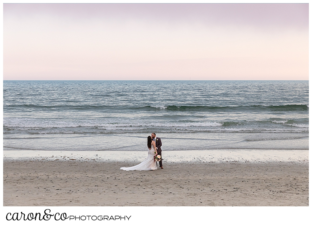 a bride and groom kiss at the water's edge, in Kennebunk Maine