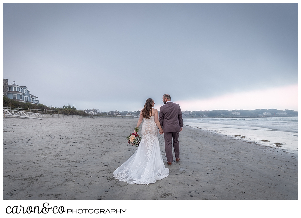 a bride and groom walk along the water at a Kennebunk Maine beach