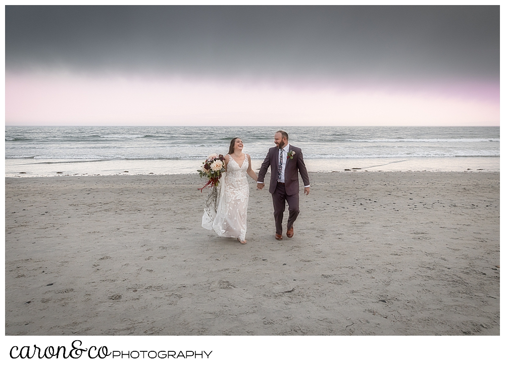 a bride and groom walking on a Kennebunk Maine beach