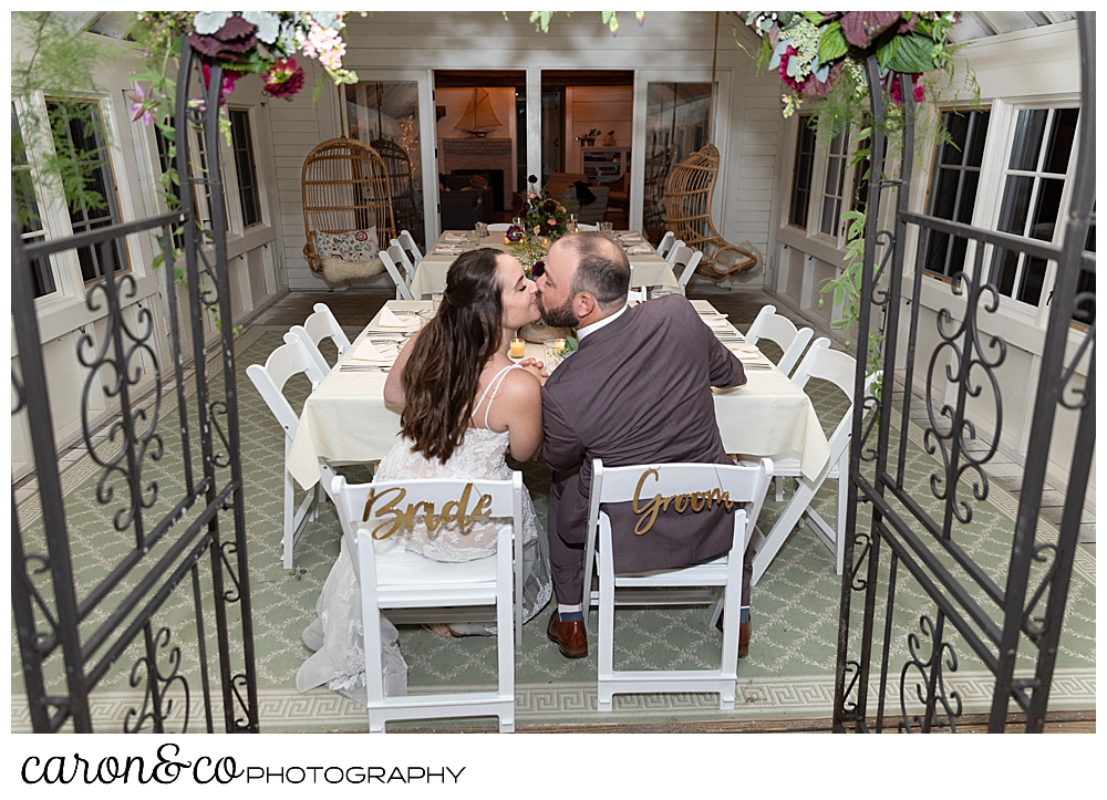 a bride and groom kiss while sitting at their charming Kennebunkport maine wedding reception