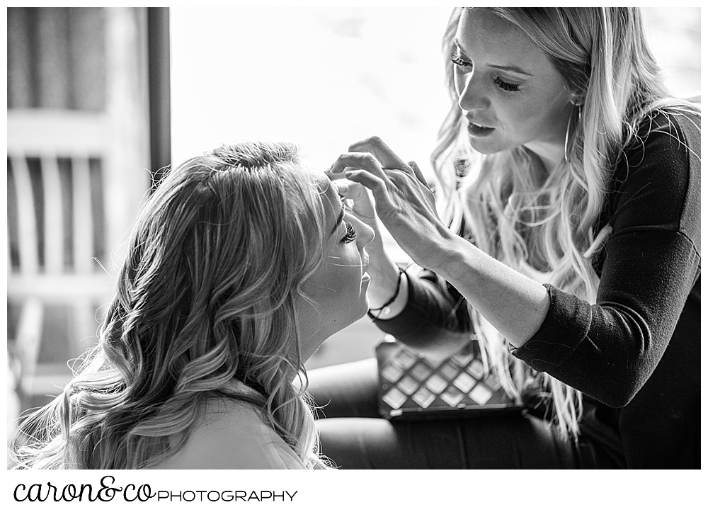 black and white photo of a makeup artist applying eye makeup on a bride