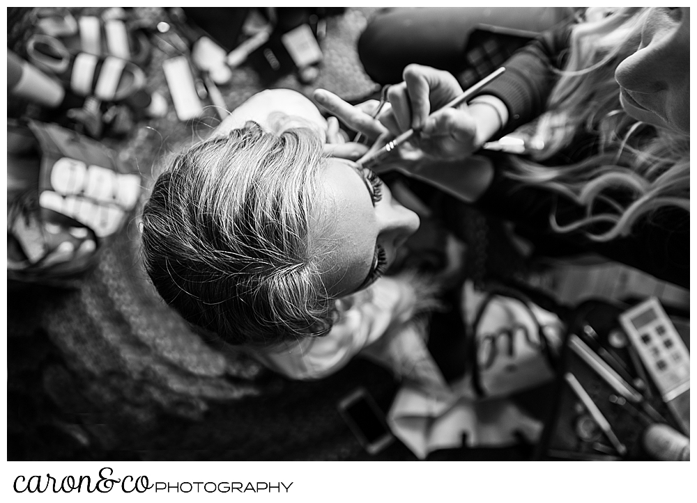 black and white photo of a makeup artist applying makeup on a bride, from an overhead perspective