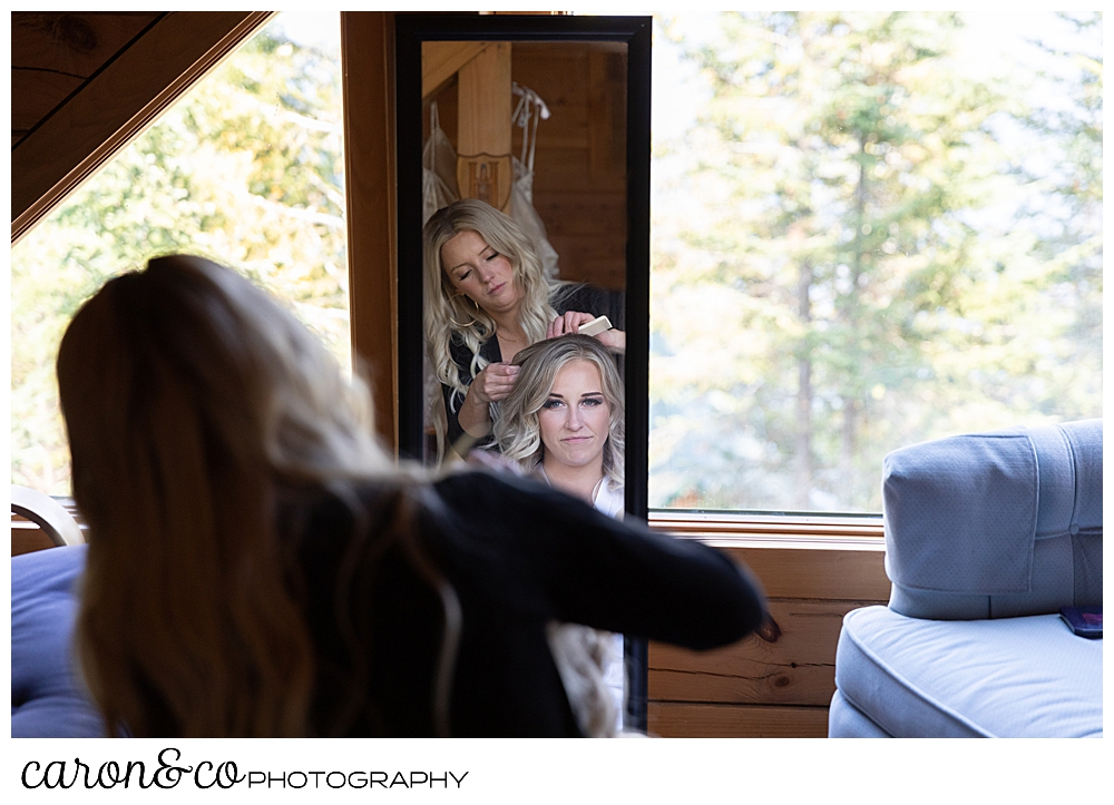 a reflection in a mirror of a bride having her hair done