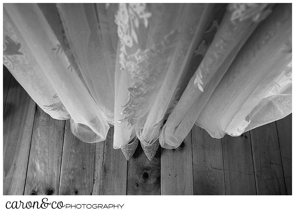 black and white photo of the skirt of a wedding dress, with a pair of sparkly shoes peeking out from below