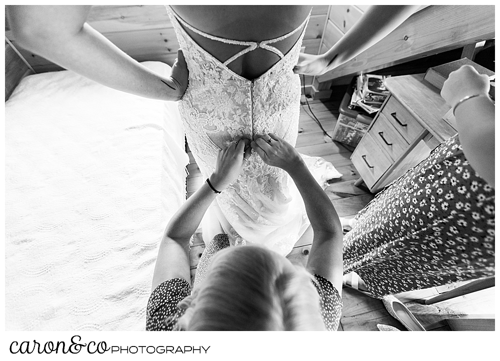 black and white image of a bride having her dress buttoned in the back