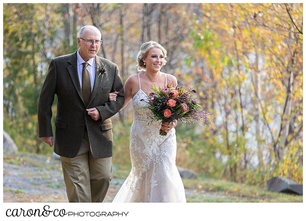 a bride and her father, arm in arm, walk down the aisle at a Rangely Maine wedding