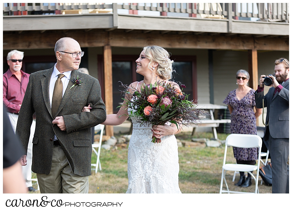 a bride and her father on their approach toward the groom at a Rangley Maine wedding ceremony