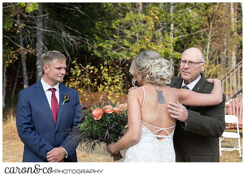 a bride and her father hug, while the groom looks on, at a Rangeley Maine wedding ceremony