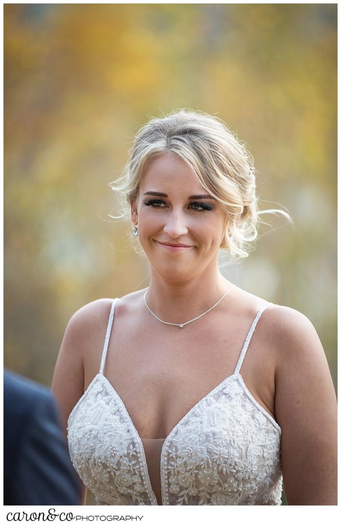 a gorgeous, blonde bride smiles at her groom during their Rangeley Maine wedding ceremony