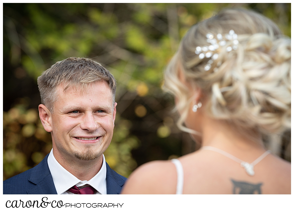 a groom smiles at his bride during their Rangeley Maine outdoor wedding ceremony