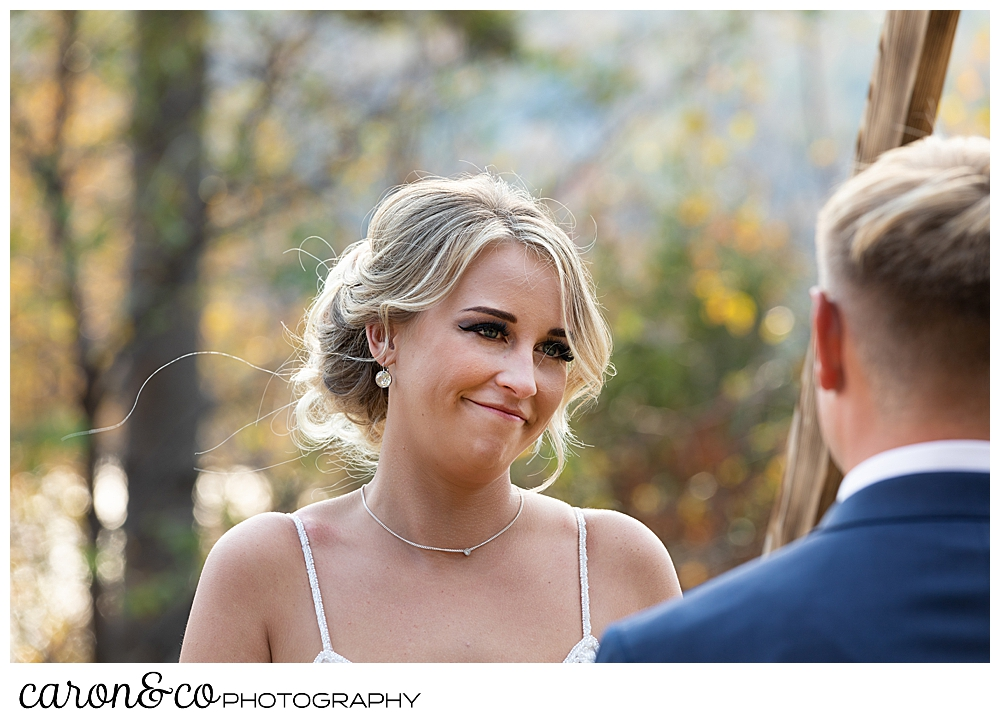 a bride smiles at her groom during their outdoor Rangeley Maine wedding ceremony