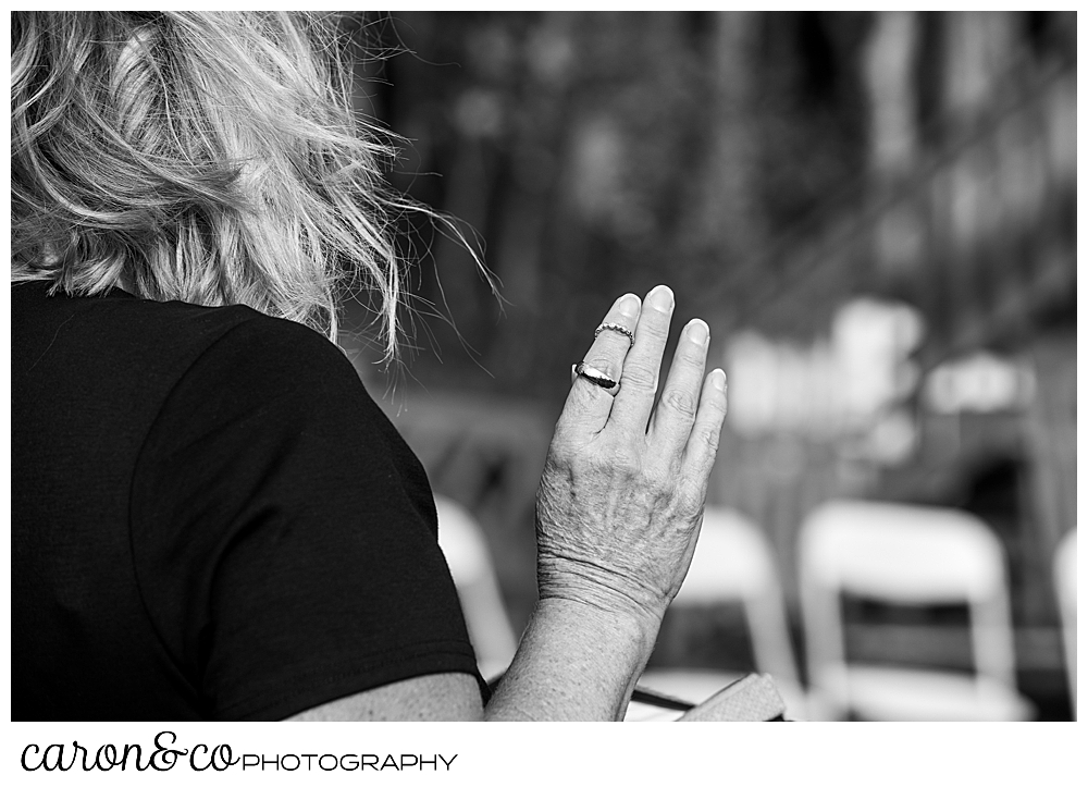a black and white photo with a wedding officiant wearing the wedding bands on her upheld hand
