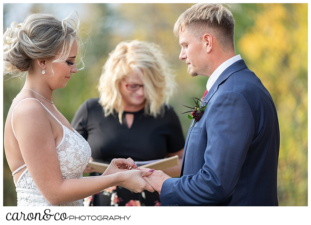 a bride puts a wedding band on her groom's finger during their outdoor Rangeley Maine wedding ceremony