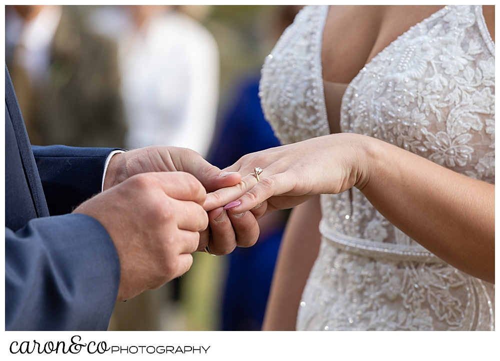 a groom puts the bride's wedding band on her finger during their Rangely Maine wedding ceremony
