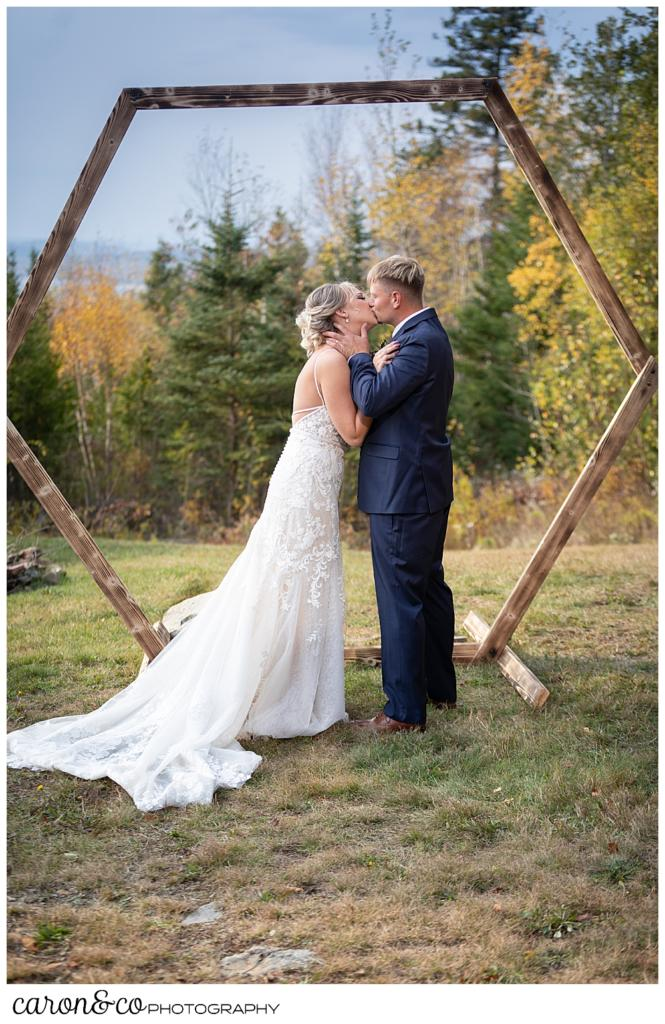 a bride and groom share their first kiss at their Rangeley Maine wedding ceremony