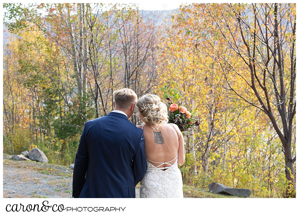 a bride and groom stand with their backs to the camera, their heads together, during their Rangeley Maine wedding day