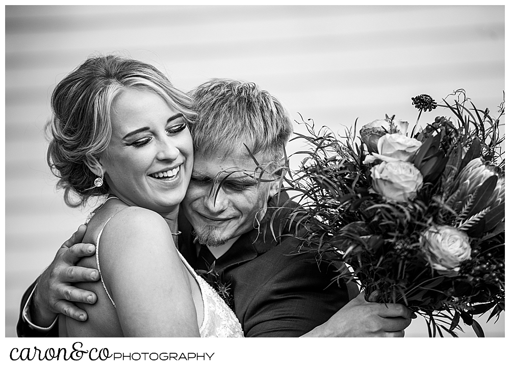 black and white photo of a bride and groom hugging after their Rangeley Maine wedding ceremony