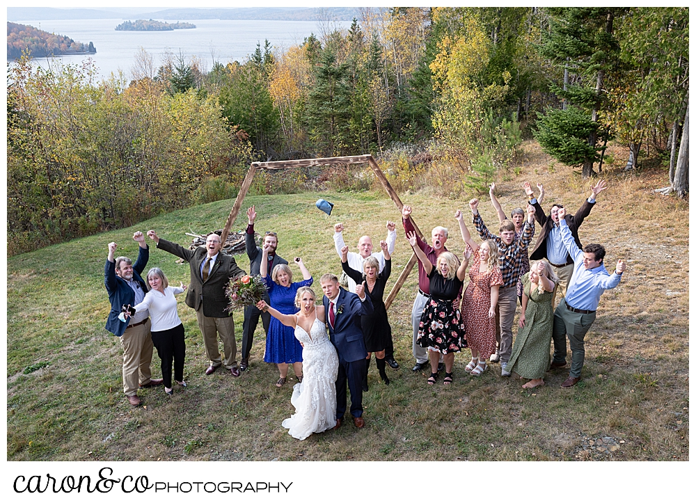 a bride and groom with their guests all cheering during a Rangeley Maine wedding