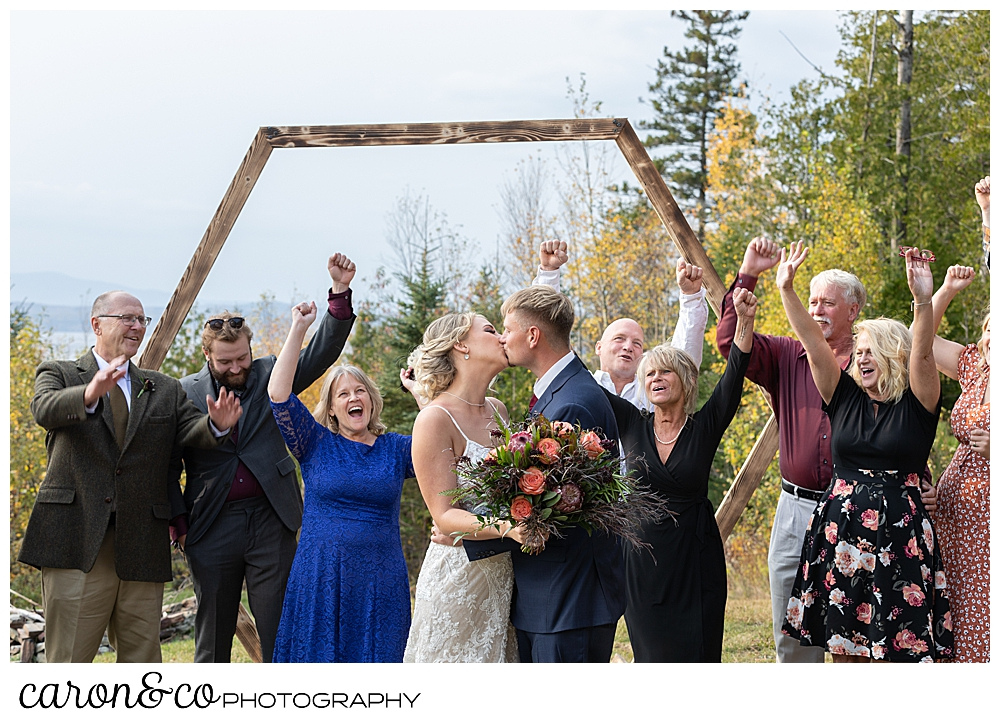 a bride and groom kiss while standing in front of their cheering families during their Rangeley Maine wedding