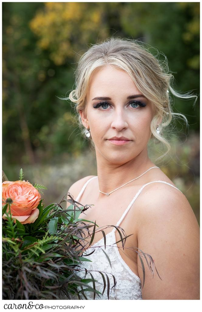 a beautiful bridal portrait of a blonde bride holding a bouquet with peach colored roses and greenery