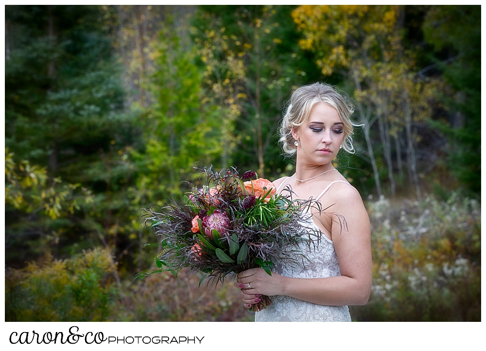 a bridal portrait of a bride her eyes closes, holding a bouquet with peach roses and greens