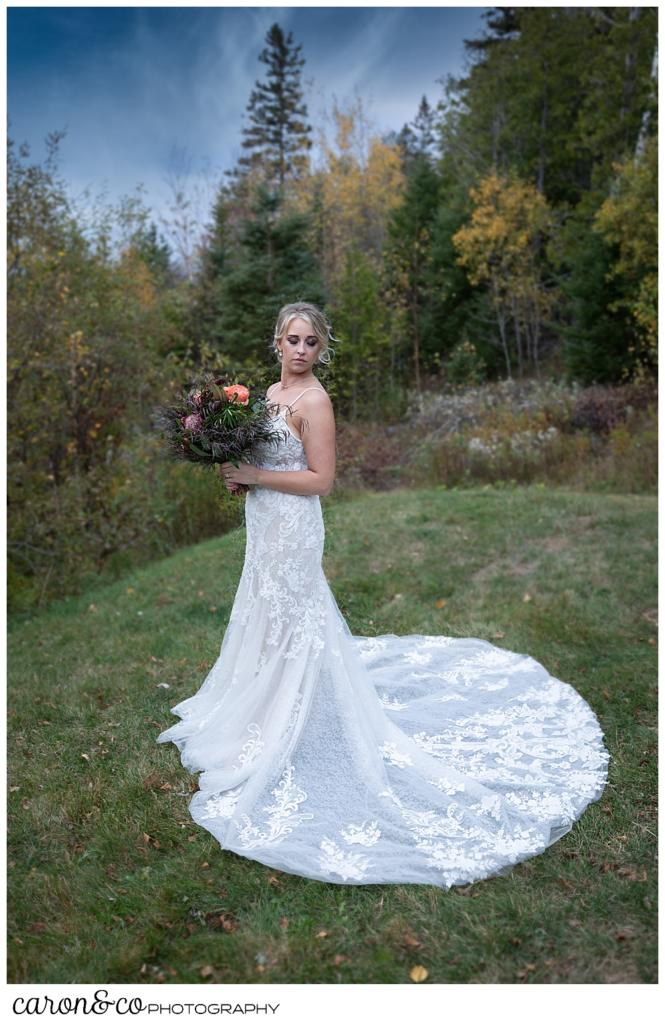 full length bridal portrait of a bride in a white dress, with a train, standing outside during her Rangeley Maine wedding