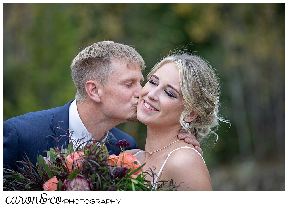 a bride smiles with her eye closed, as her groom kisses her cheek