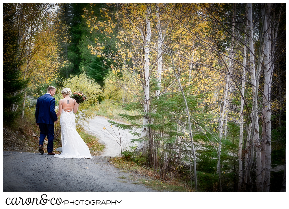 a bride and groom walk, with their backs to the camera, hand in hand down a dirt road in the fall foliage during a Rangeley Maine wedding