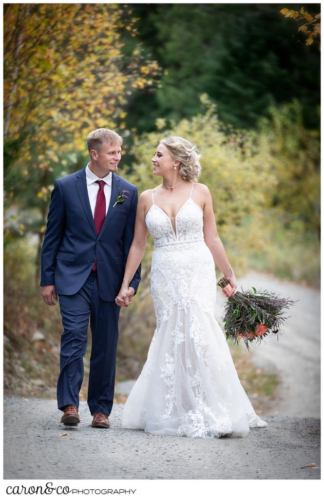 a bride and groom walking hand in hand in the fall foliage at a Rangeley Maine wedding