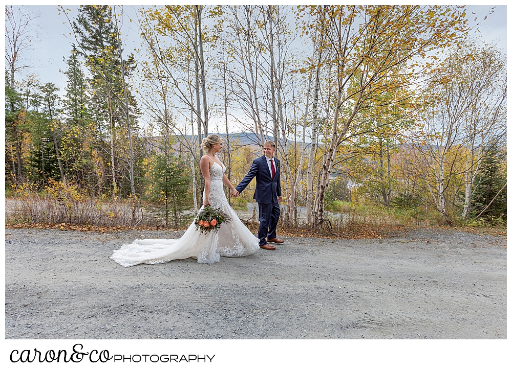 a bride and groom walk past, hand in hand in a Rangeley Maine wedding fall foliage
