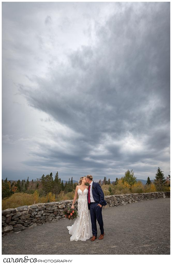 a bride and groom kiss with a dramatic sky behind them at a Rangeley Maine wedding