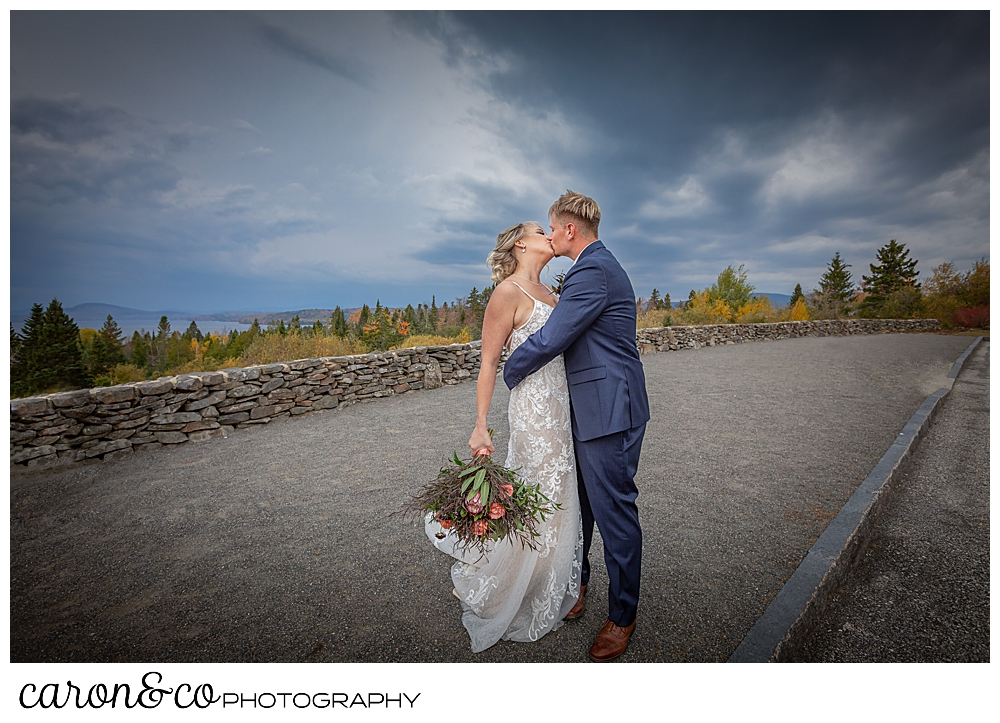 a bride and groom kiss with foliage and dramatic skies in the background during a Rangeley Maine wedding