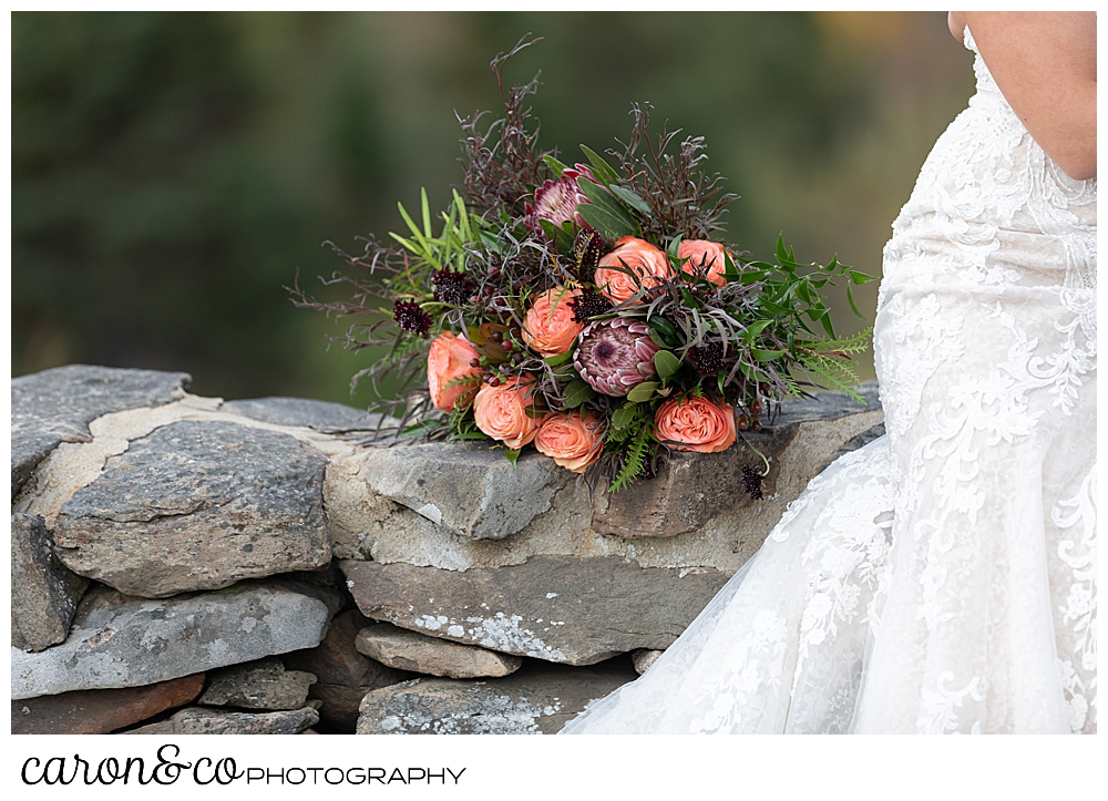 a bride's bouquet of peach roses and greenery, sits on a stone wall