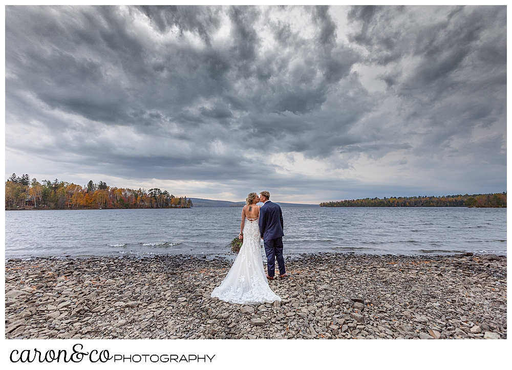 a bride and groom kiss on the shore of Rangeley Lake,