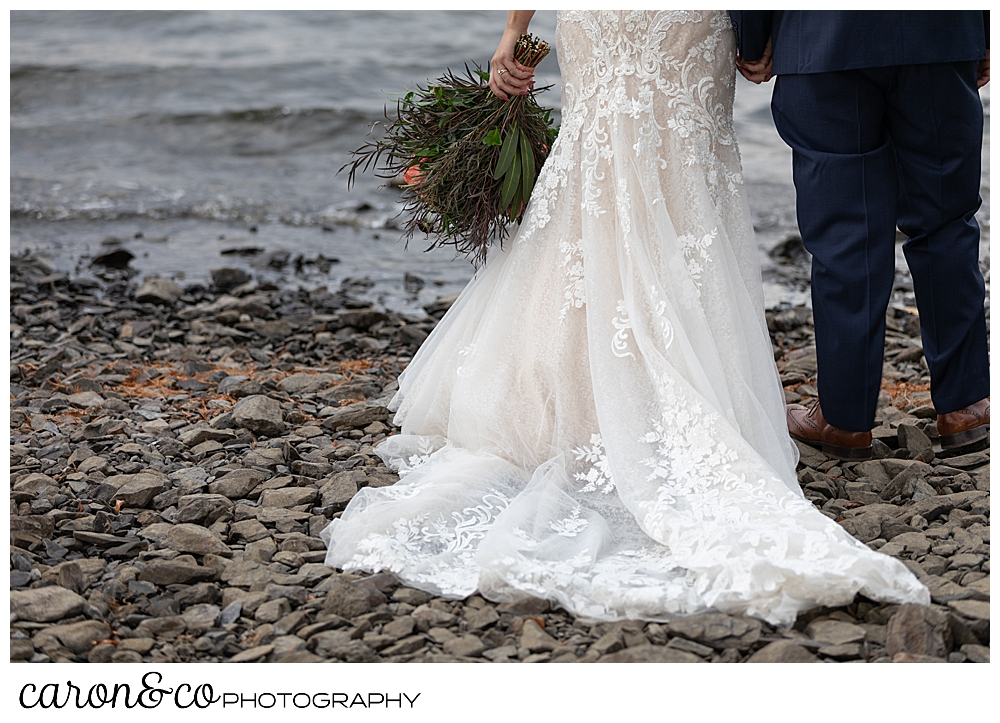 the back of a Martina Liana wedding dress, as a bride and groom stand with their backs to the camera, on the shores of Rangeley Lake, Rangeley Maine
